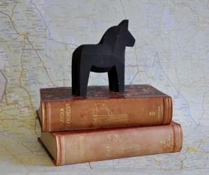 En trähäst stående på två böcker med Dalakarta som bakgrund