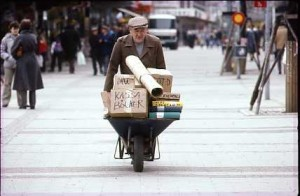 En man på en stadsgata skjuter en skottkärra fylld med kartonger och pärmar som innehåller arkivhandlingar